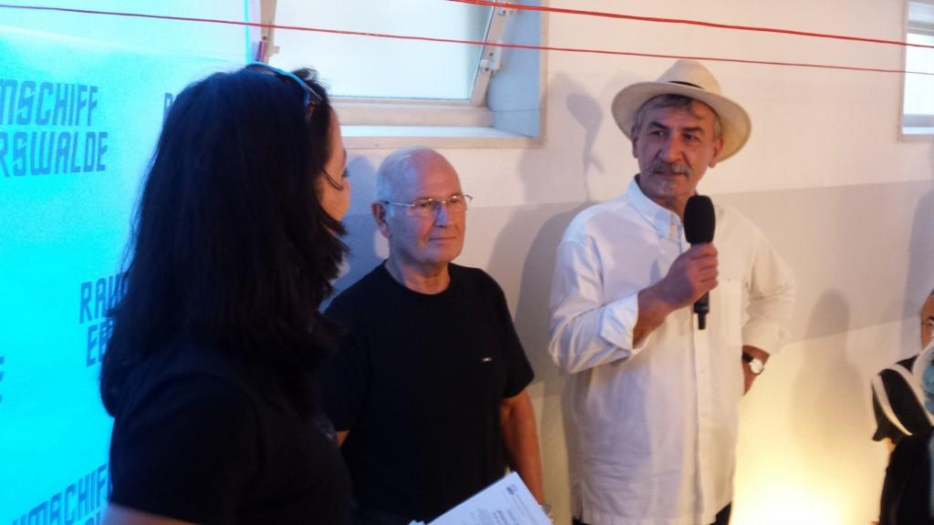 Zum Abschluss nochmal ganz große Kunst: Der Choriner Zeichner und Maler Andreas Bogdain hat die USS Eberswalde aus dem Podcast ins reale Leben geholt. Ernst Meincke hat die Ehre, das Modell zu enthüllen